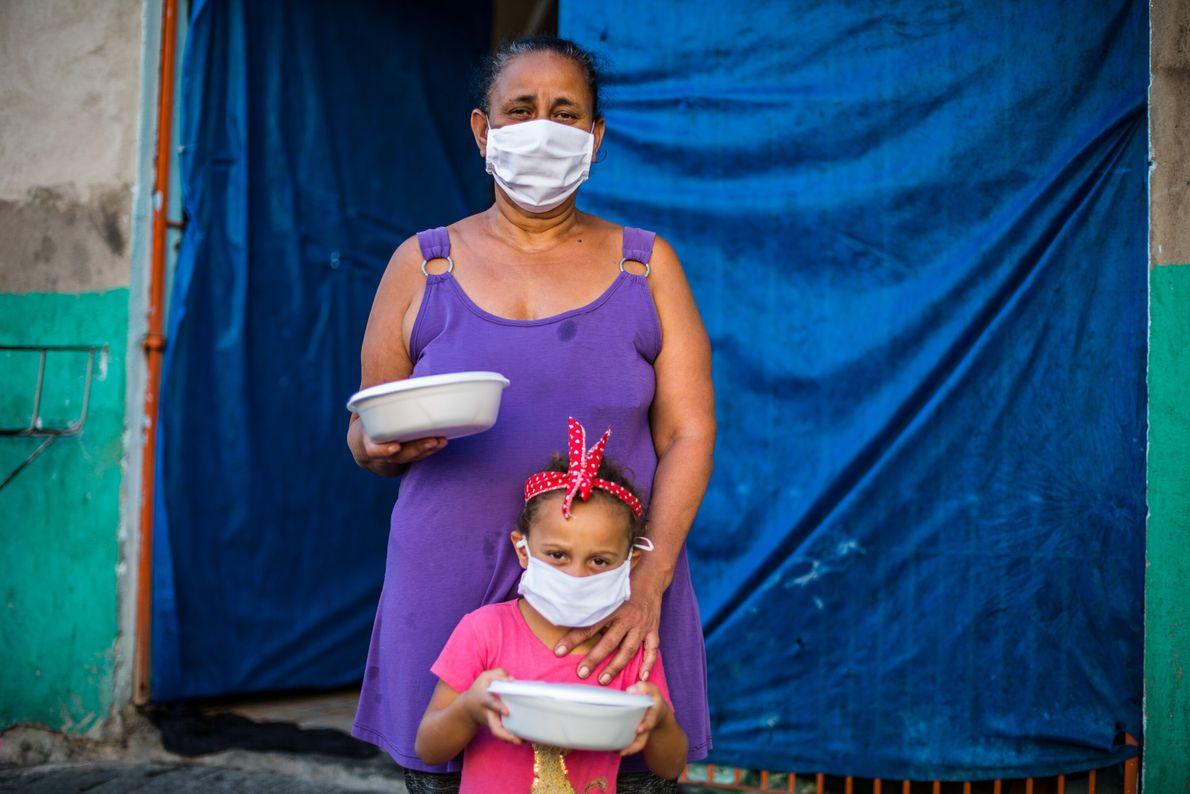 Sandra Fátima Gomes e sua neta, moradoras do Jardim Robru, busca marmitas produzidas pelo grupo O ...