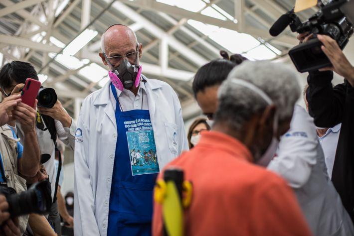 Ao lado de jornalistas, o padre Julio Lancellotti observa vacinação de moradores de rua no Centro Comunitário ...