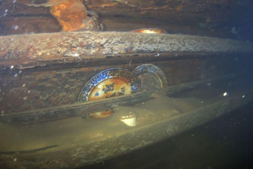 Pratos ainda nas prateleiras, como se estivessem prontos para a próxima refeição. O lodo cobre grande ...