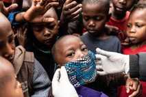 Trabalhador humanitário coloca uma máscara em um menino enquanto distribui alimentos para famílias vulneráveis em Nairóbi, ...