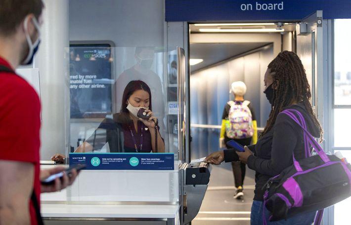 Uma agente de embarque da United Airlines auxilia os passageiros posicionada atrás de um escudo plástico ...