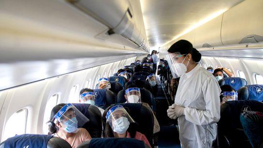 Comissária de bordo da Buddha Air veste um traje de proteção e protetor facial durante um ...