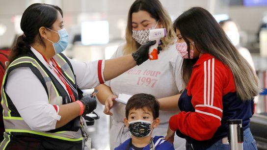 Viagens aéreas podem impor riscos de exposição ao novo coronavírus. Funcionária verifica a temperatura de uma ...