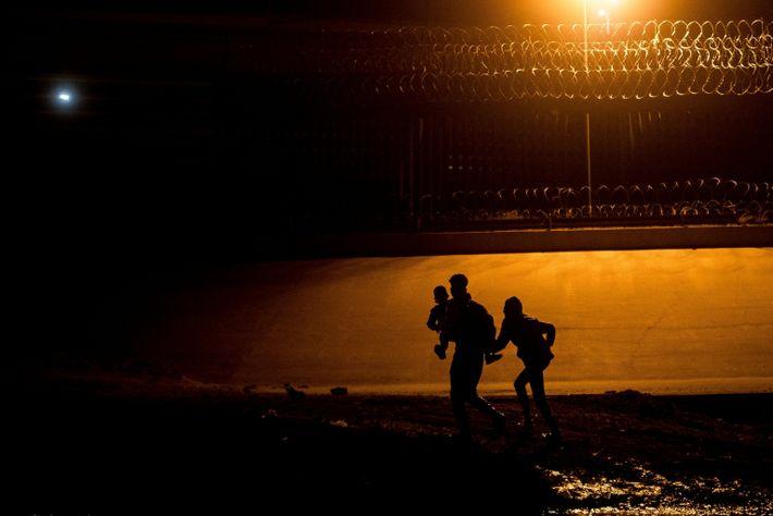 Foto noturna de silhueta de imigrantes tentando atravessar a fronteira dos EUA com México em Ciudad ...