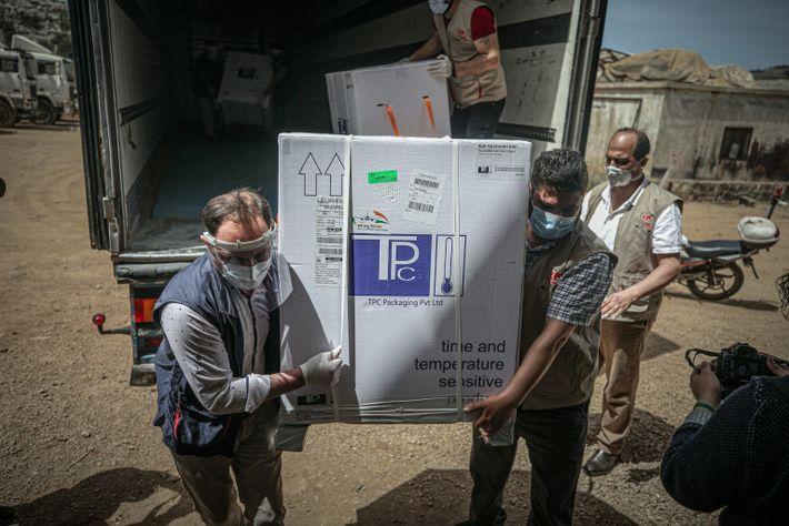 Funcionários em Idlib, na Síria, descarregam mais de 50 mil doses de vacinas contra covid-19 no ...