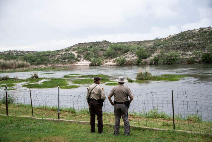 Dois patrulheis da imigração americanos observam rio na fronteira dos EUA com México