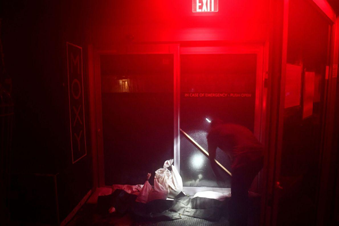 Os funcionários de um hotel reforçam o fechamento da porta para evitar que ela se abra ...