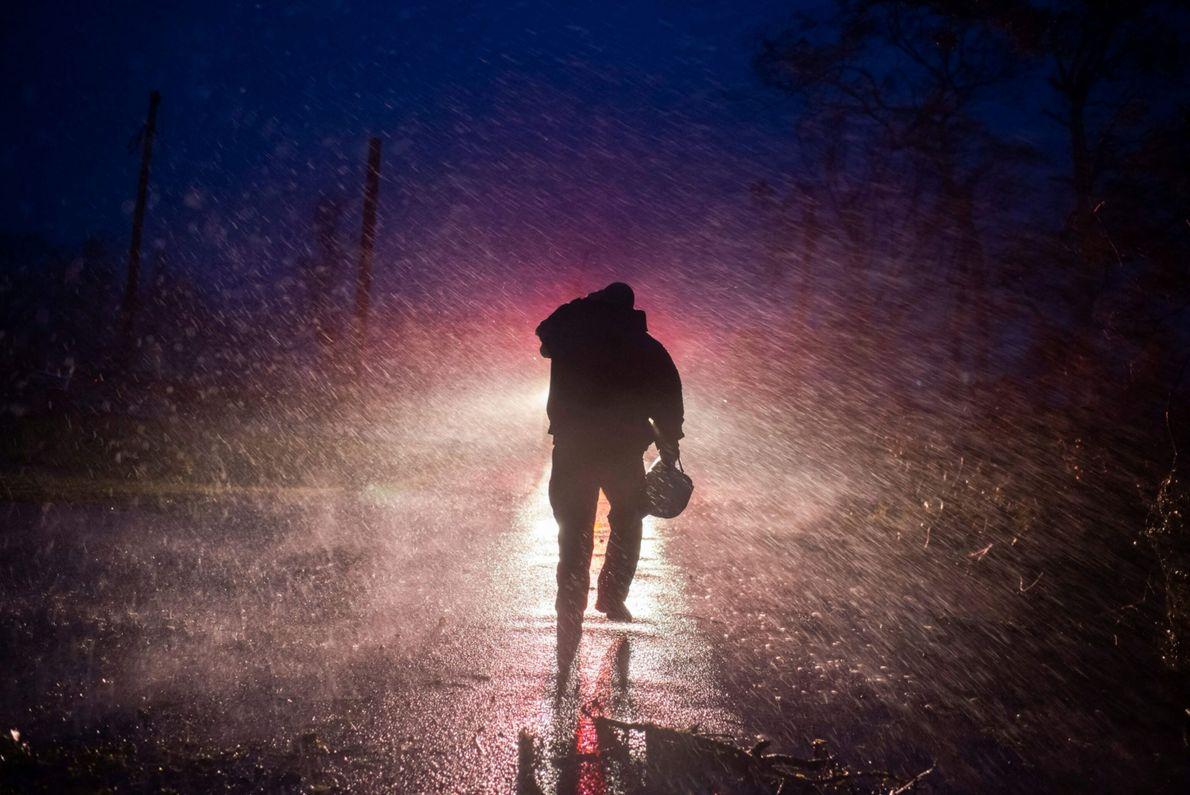 O chefe dos bombeiros de Montegut, Toby Henry, volta para seu caminhão na chuva, enquanto os ...
