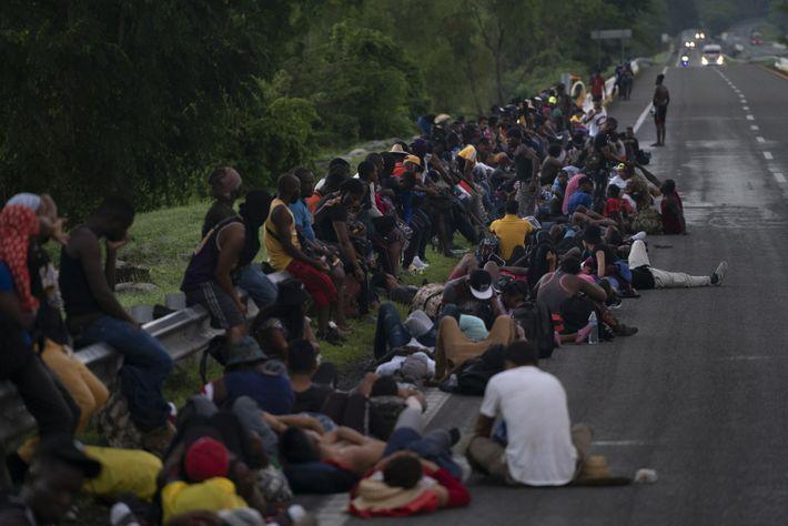 Dezenas de imigrantes haitianos sentados nas margens de uma rodovia asfaltada no México