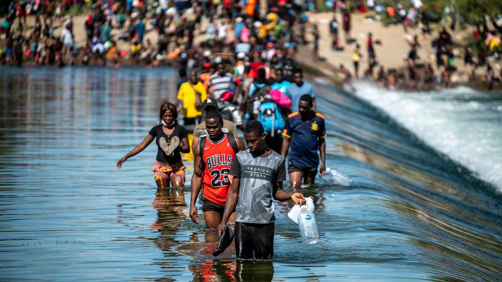 Foto de imigrantes haitianos atravessando um rio que é fronteira dos EUA com o México