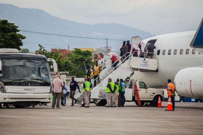 Foto de haitianos desembarcando por escada de um avião depois de serem deportados