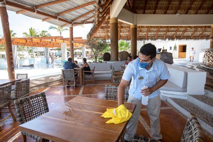 Garçom de um restaurante em La Paz, no México, higieniza uma mesa. O turismo é uma ...
