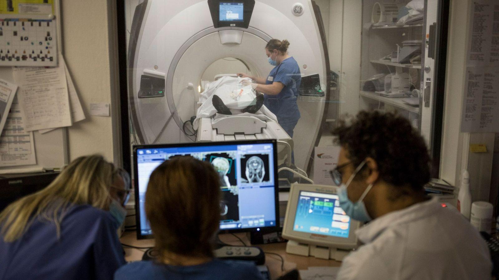 O radiologista Arshid Azarine (à direita) realiza uma ressonância magnética com equipe médica em um paciente ...