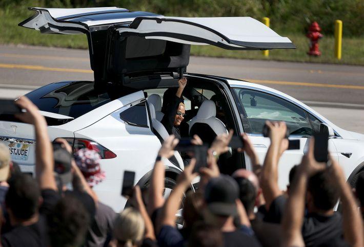 mulher acena para multidão de dentro de um carro com portas que abrem para cima