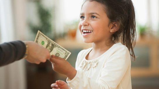 Mãe entrega nota de um dólar à menina, em Nova York.
