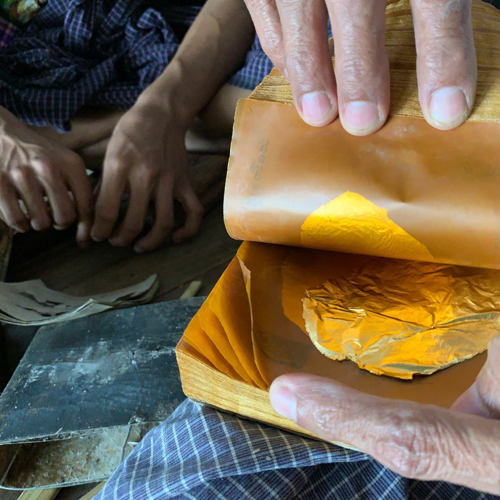 Na King Galon Gold Leaf Workshop, em Mandalai, Mianmar, grãos de ouro agrupados entre folhas de ...