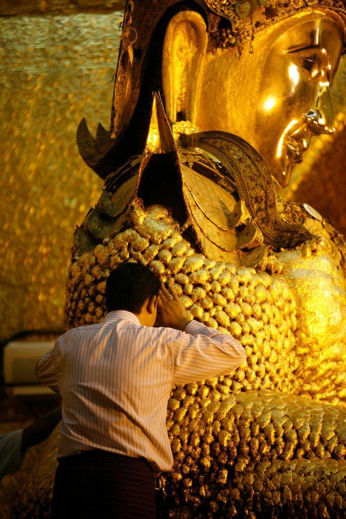 Parte das folhas de ouro da oficina de King Galon cobriu a estátua de Buda com ...