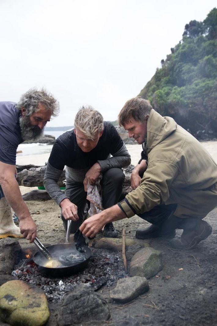 Os pescadores locais Fluff (E) e Zane (D) ensinam Gordon Ramsay (centro) a cozinhar pāua, um ...
