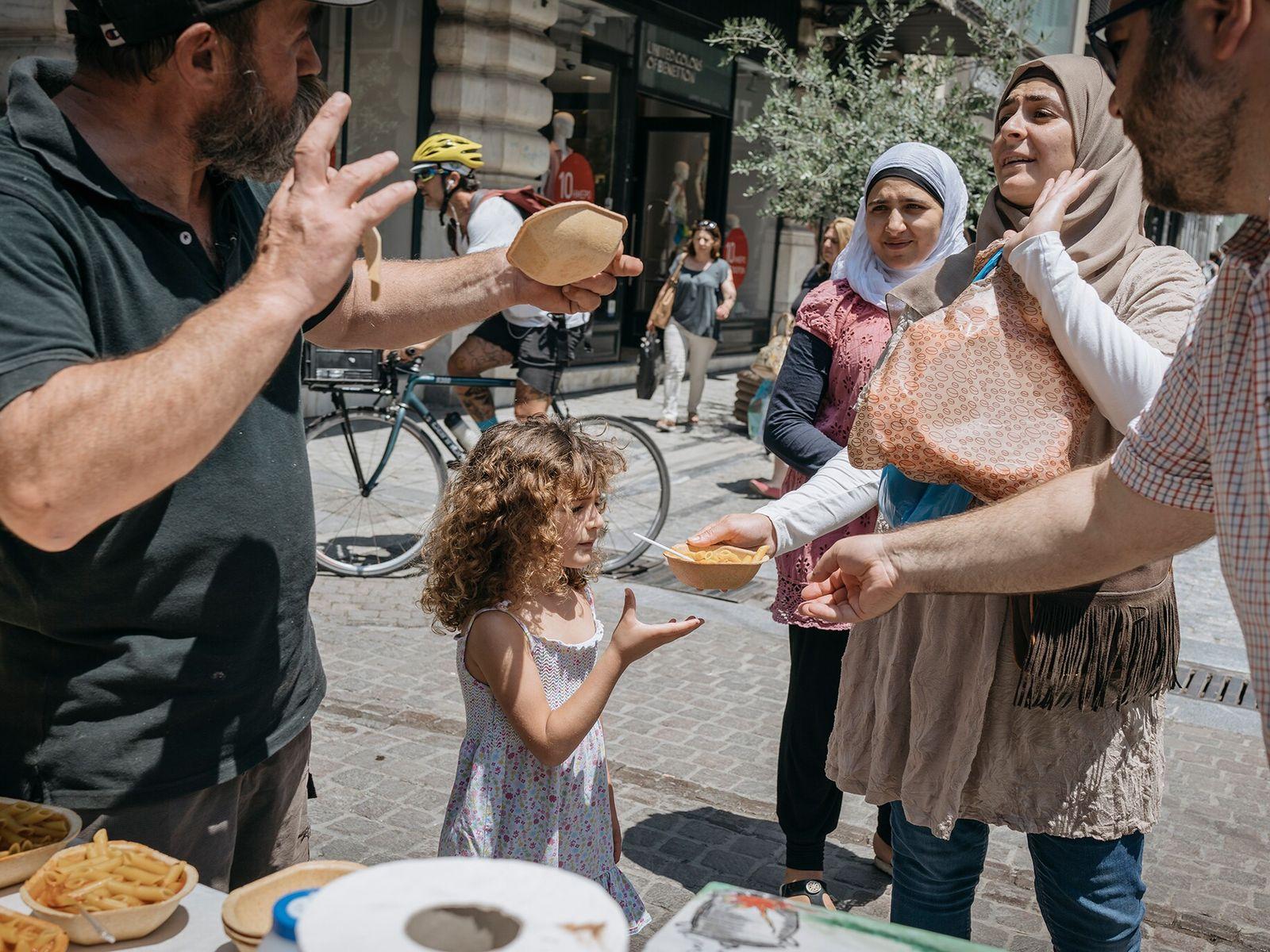 Konstantinos Polychronopoulos oferece uma tigela de sopa a refugiados que passam pela rua Ermou, em Atenas, ...