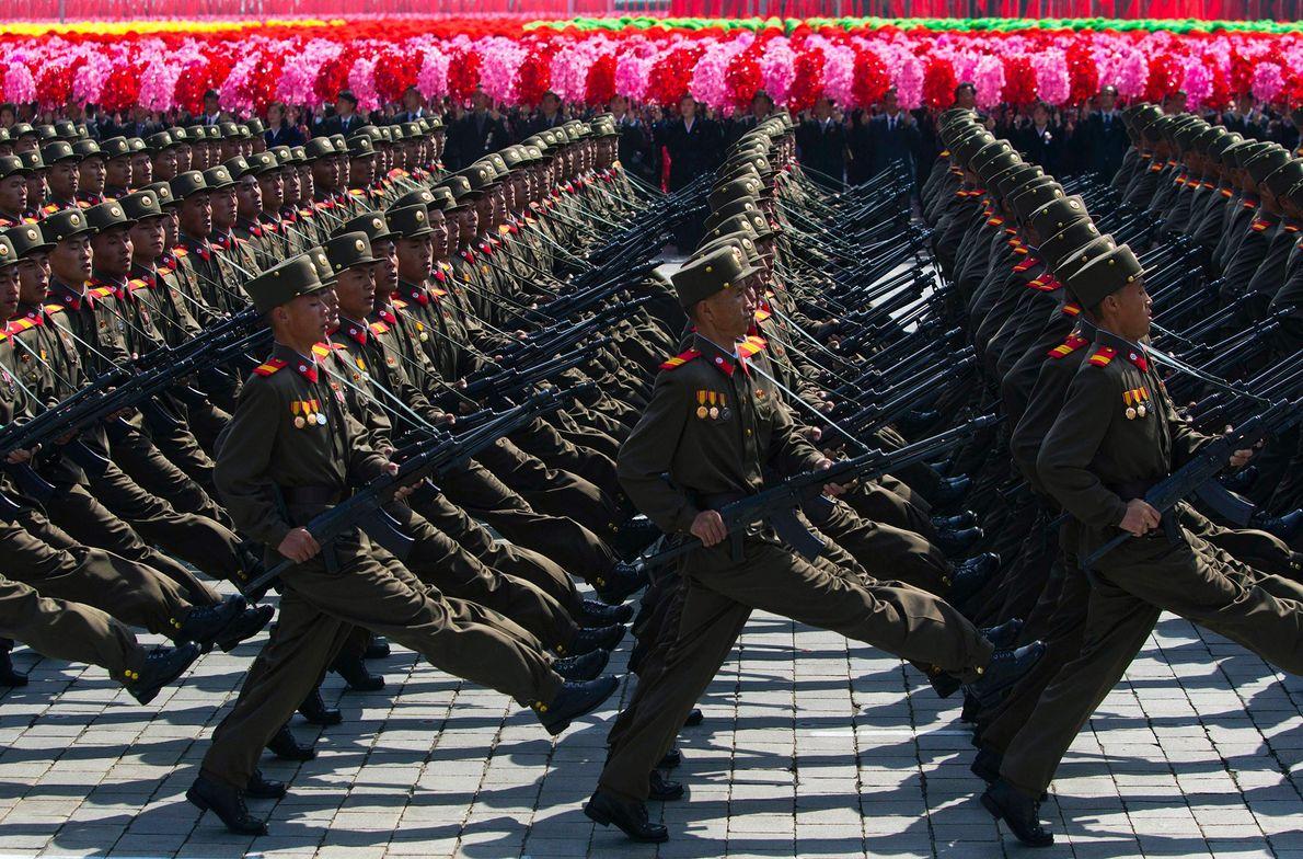 Soldados norte-coreanos marcham em frente a uma multidão de civis que acenam com flores durante um ...