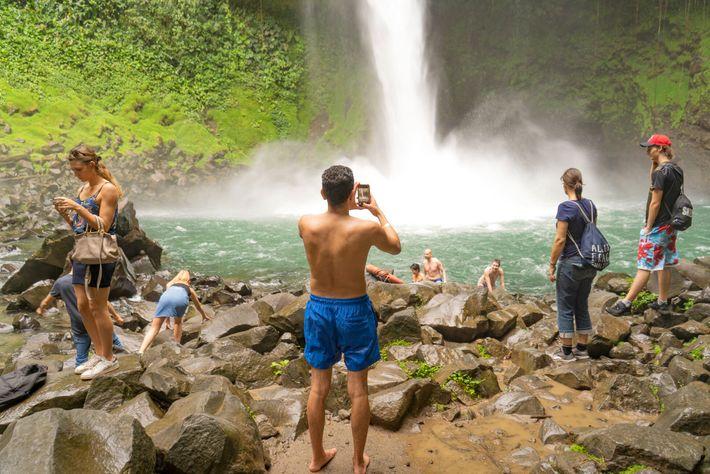Turistas tiram fotos e nadam no rio Fortuna, no Parque Nacional Vulcão Arenal, na Costa Rica. ...