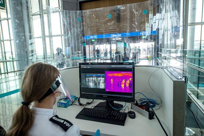 Uma oficial de segurança do Aeroporto de Istambul utiliza um leitor de temperatura para escanear os ...