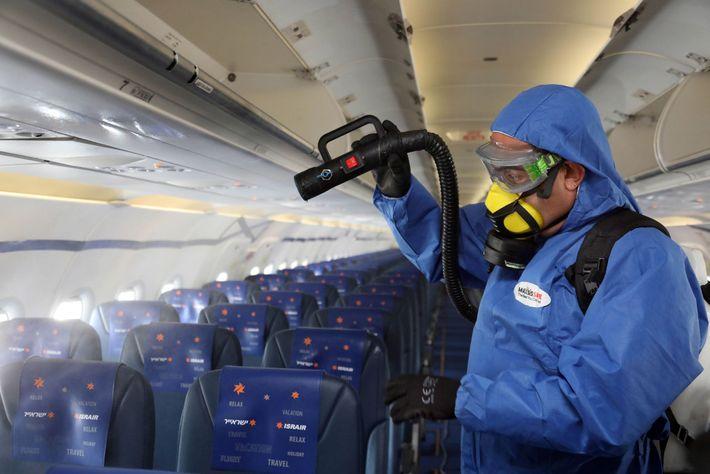 Um funcionário com equipamento de proteção desinfeta um avião da Asrair Airlines no Aeroporto Internacional Ben ...