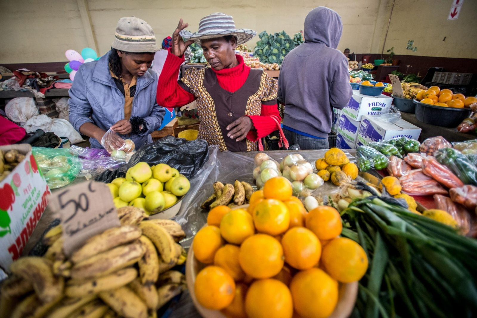 Women buying produce at the Manzini Wholesale Produce and Craft Market in eSwatini, Africa.