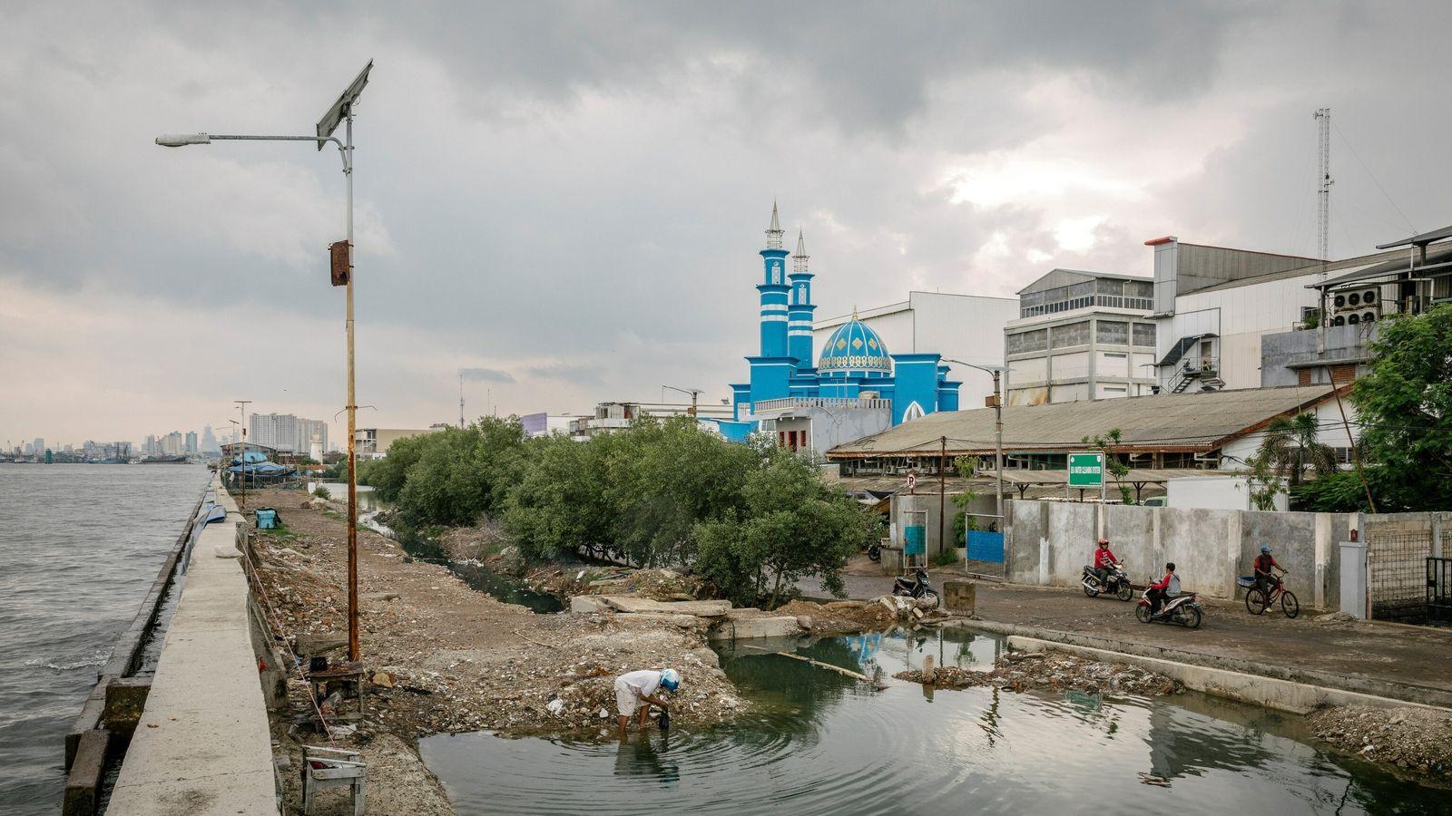 O muro de contenção na Baía de Jacarta evita que lojas, casas e mesquitas sejam inundadas ...
