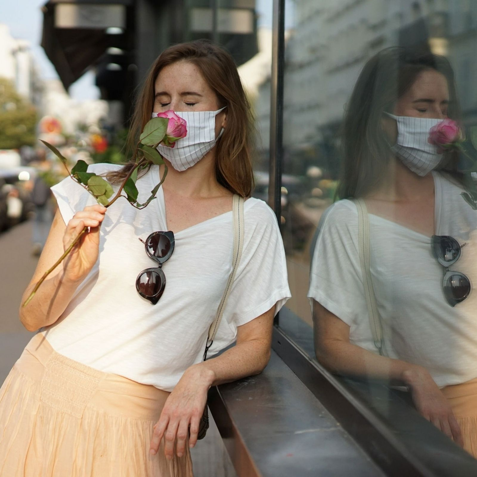 Mulher usando máscara de proteção cheira uma rosa em Paris.