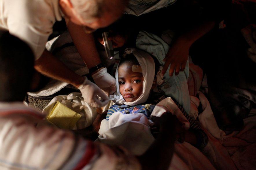 As equipes de emergência cuidando de uma criança pequena um dia após um terremoto de magnitude ...