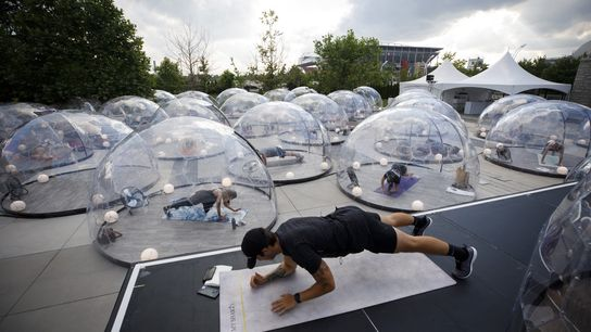 Pessoas participam de uma aula de ioga ao ar livre no Hotel X, dentro de cúpulas ...