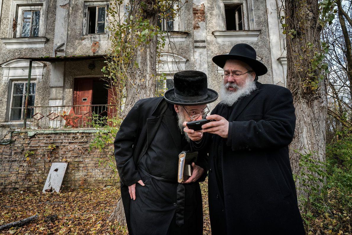 Em frente à antiga sinagoga, Yitz Twersky mostra algumas de suas fotografias antigas ao Rabino Leibel ...