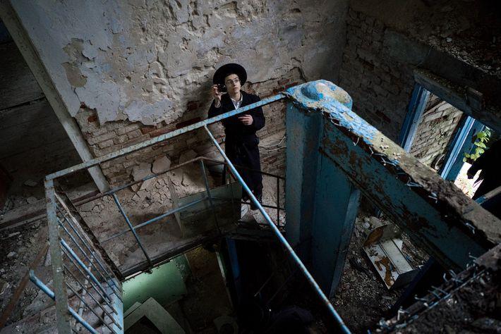 Um visitante na sinagoga abandonada de Chernobyl pausa para tirar uma foto.