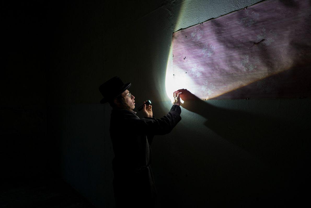 Um visitante direciona sua lanterna para analisar as paredes da sinagoga abandonada.