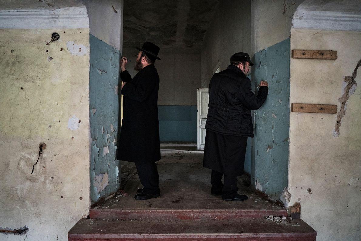 Após uma longa viagem, dois peregrinos escrevem seus nomes nas históricas paredes da antiga sinagoga.