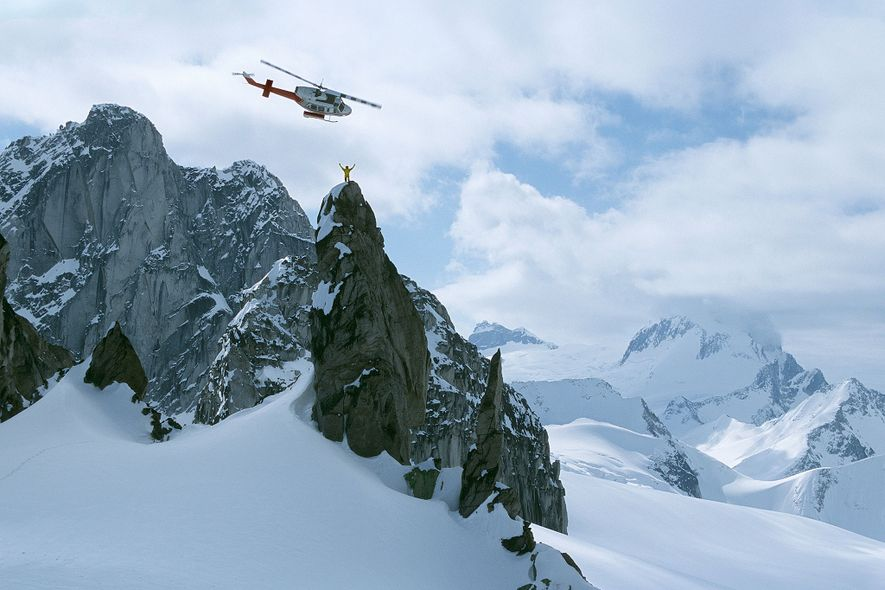 Um guia de heli-ski acena do topo do pináculo Osprey, nas montanhas Purcell, no Canadá.