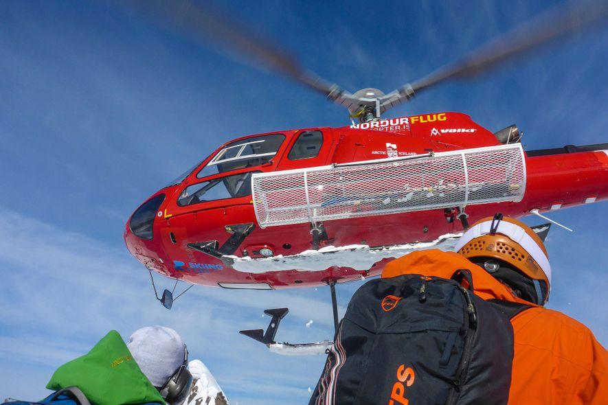Um helicóptero parte após deixar esquiadores da Península Troll na Islândia.