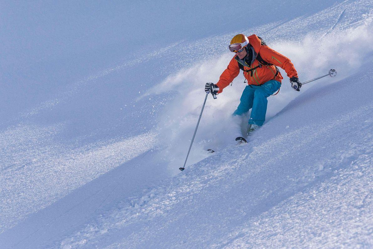 A neve voando de um esquiador na Península Troll, na Islândia.