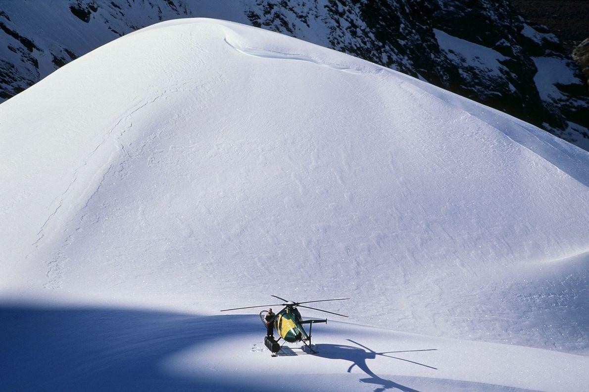 Um piloto de helicóptero espera os esquiadores voltarem de uma descida na Nova Zelândia.