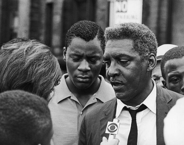 Afro-americano ativista dos direitos civis, Bayard Rustin fala com um repórter durante as rebeliões do Harlem ...