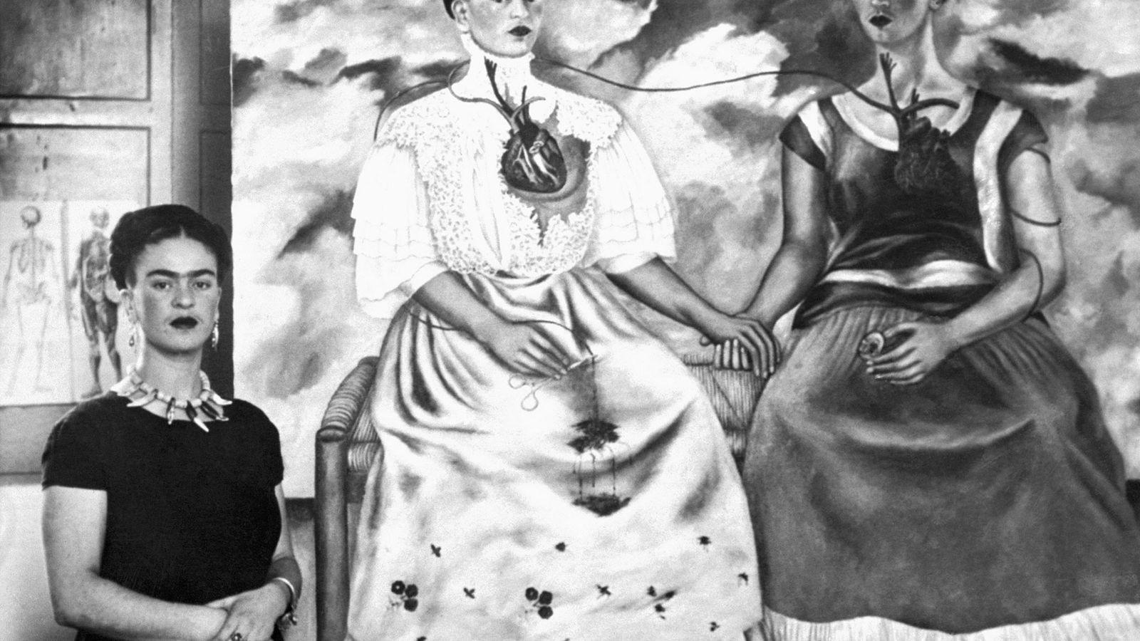 """Frida Kahlo de pé ao lado de sua pintura intitulada """"Me Twice"""" em 1939."""