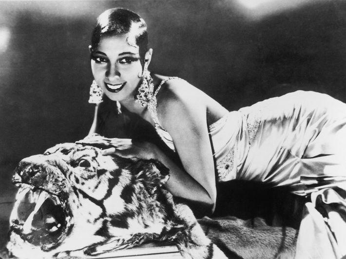 Cantora e compositora Josephine Baker esticada em um tapete de tigre com um vestido de seda ...