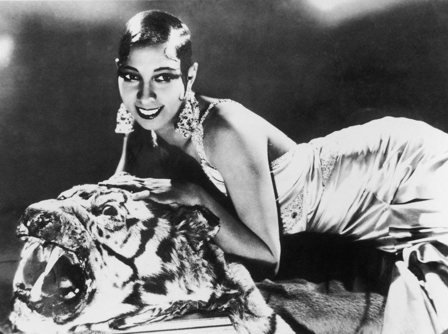 Cantora e compositora Josephine Baker esticada em um tapete de tigre com um vestido de seda e brincos de diamante em meados dos anos 1920.