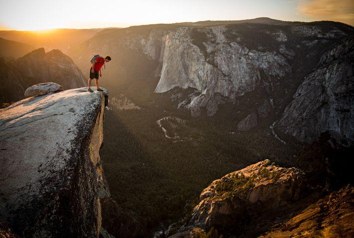 Honnold espia pela beirada de Taft Point, do outro lado do Vale Yosemite a partir da ...