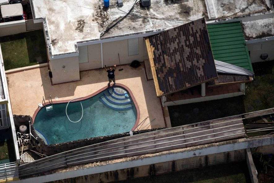 O pai do fotógrafo acena para enquanto o filho sobrevoa a região atingida pelo furacão Maria. ...