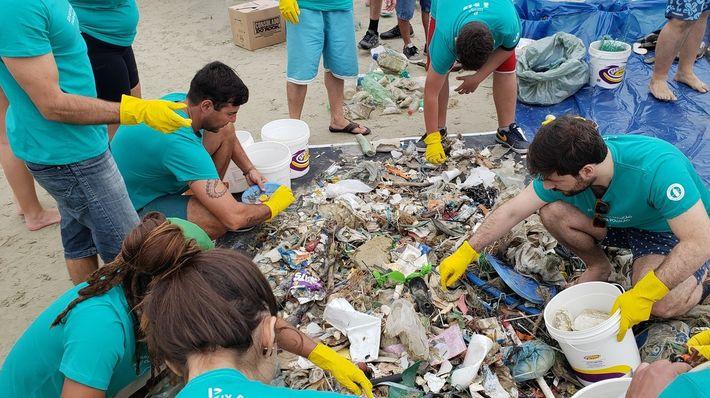 Voluntário recolhem lixo durante mutirão de limpeza organizado na praia do Guaraú, em Peruíbe, SP.