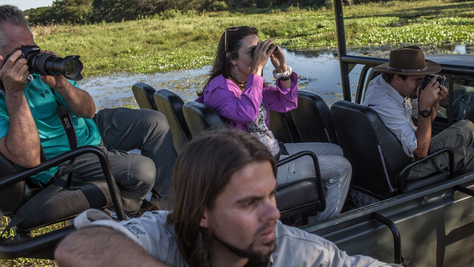 Grupo de turistas usa binóculos e câmeras para tentar avista uma onça-pintada na fazenda Caiman, no ...