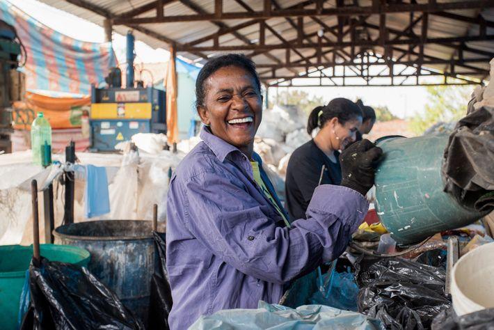 Cooperada sorri enquanto realiza triagem de materiais recicláveis na Coopersonhos, em Nova Odessa (SP).