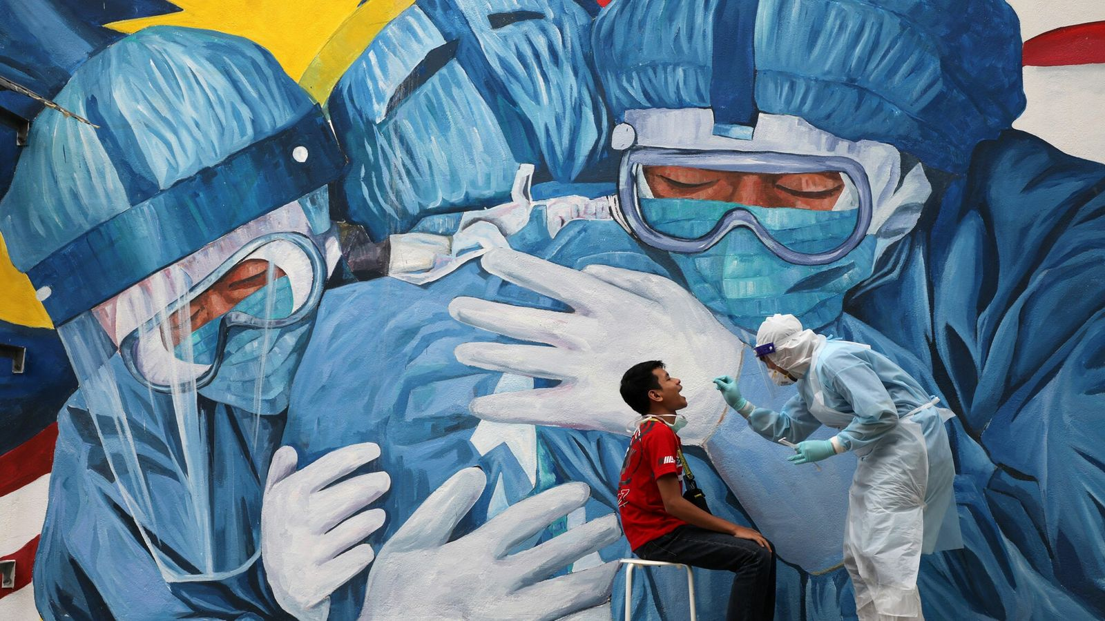Médico coleta amostra de um homem para teste de covid-19 na frente da clínica Ajwa em Shah ...